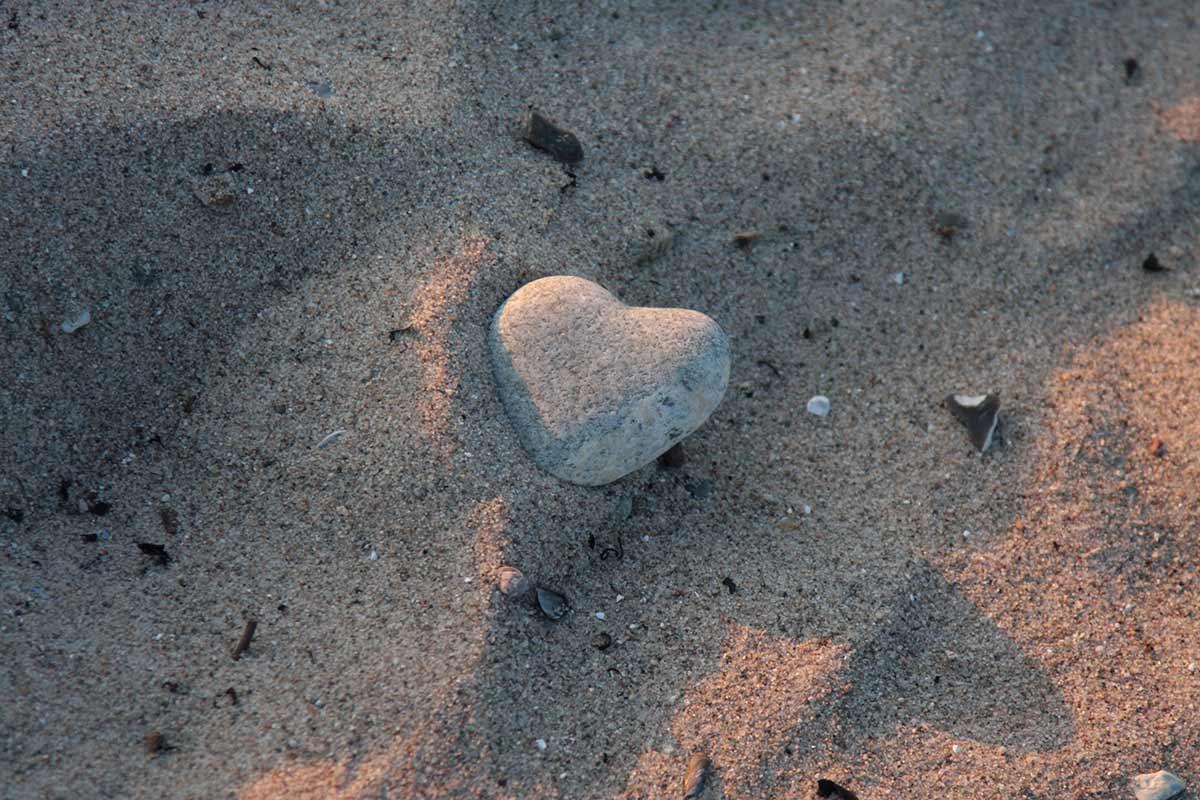 Stein als Herz geformt im Sand